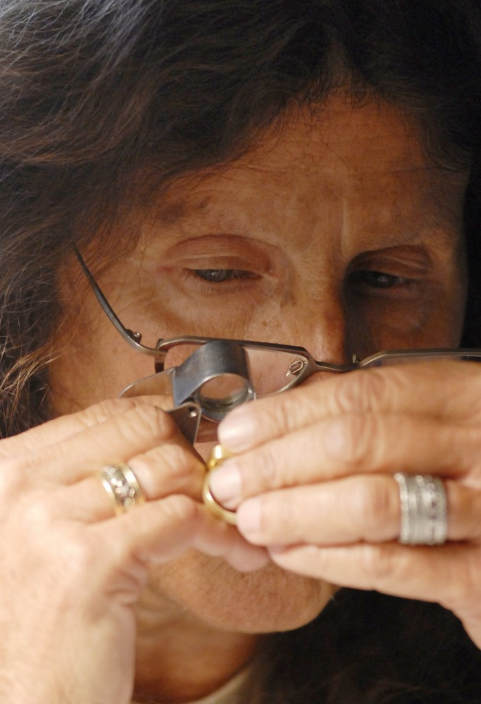 Appraiser Arlene Abelow of Los Angeles examines jewelry during the Buying Road Show at Best Western Merry Manor Inn in South Portland.