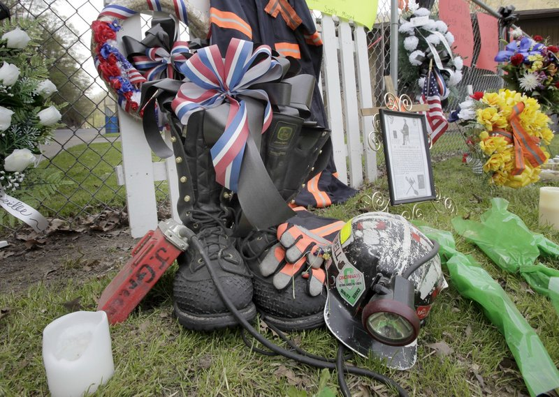A miner's boots, helmet and gloves appear in a memorial in Whitesville, W.Va., on Tuesday, for the miners who died in an explosion at the Upper Big Branch mine in Montcoal, W.Va., a week ago Monday. Teams early Tuesday finished recovering the last of 29 miners killed in the disaster.