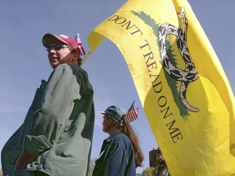 """Tom and Debbie Barry of Lisbon Falls hold a Gadsden flag emblazoned with the words """""""