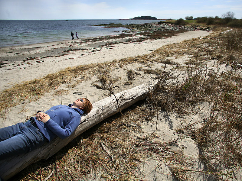 Jennifer Gerow of Portland soaks up the sun during a visit this week to the southern end of Crescent Beach in Cape Elizabeth. The Sprague Corp. owns the state park's access road, about a quarter of the parking lot and 1,000 feet of ocean frontage.