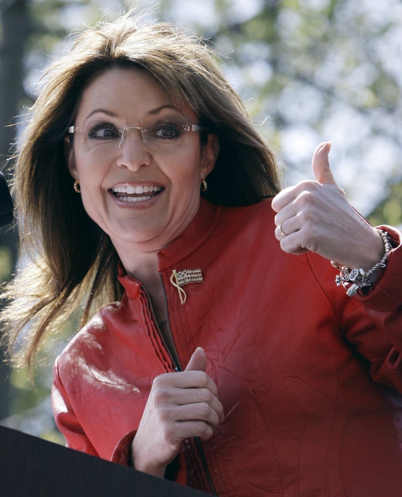 Sarah Palin gestures toward her husband as she addresses a tea party crowd Wednesday in Boston.