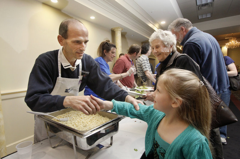 Kai Myers, 6, of Portland shakes hands with Gov. John Baldacci at the Italian Heritage Center in Portland, where he hosted a spaghetti supper to benefit Preble Street.