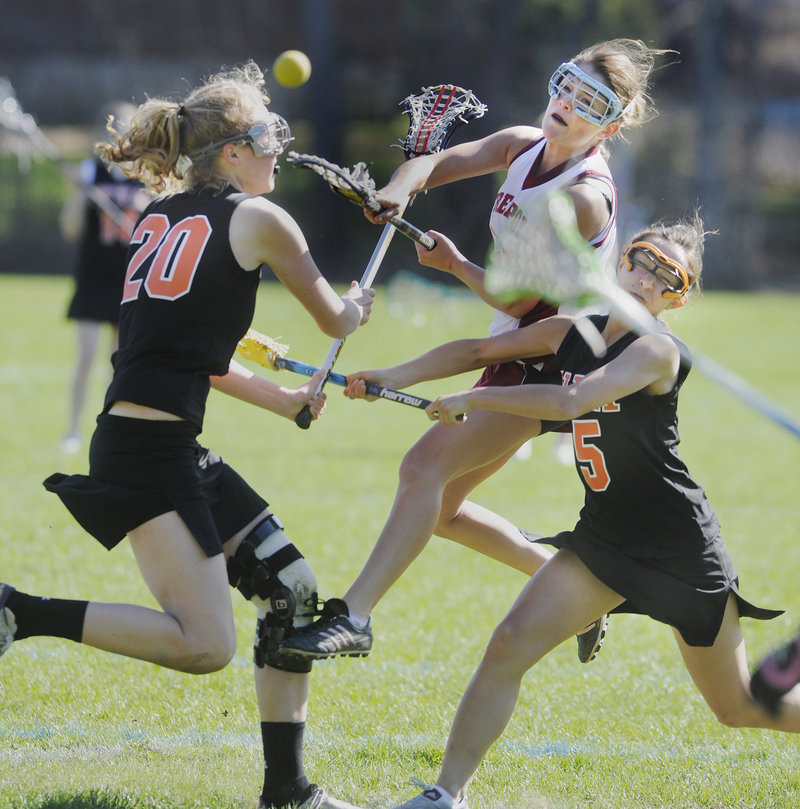Shelby Colvin of Freeport looks for room between Lilly Wellenbach, left, and Hannah Twombly of North Yarmouth Academy to get off a shot. NYA won the girls' lacrosse opener on the road, 11-4.