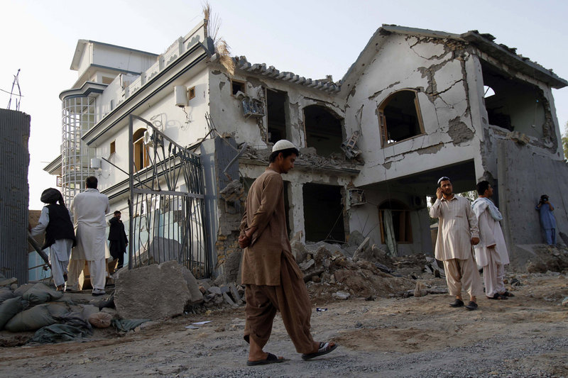 Afghans walk by a house destroyed in a suicide bombing in Kandahar, Afghanistan, on Friday. Fear has gripped the southern city ahead of NATO's upcoming offensive.