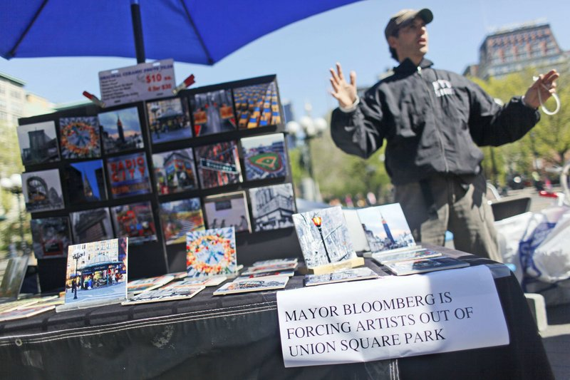 Artist and vendor Joel Kaye expresses his sentiments with a sign at his table in Union Square. Mayor Michael Bloomberg has proposed limiting art vendors' tables.