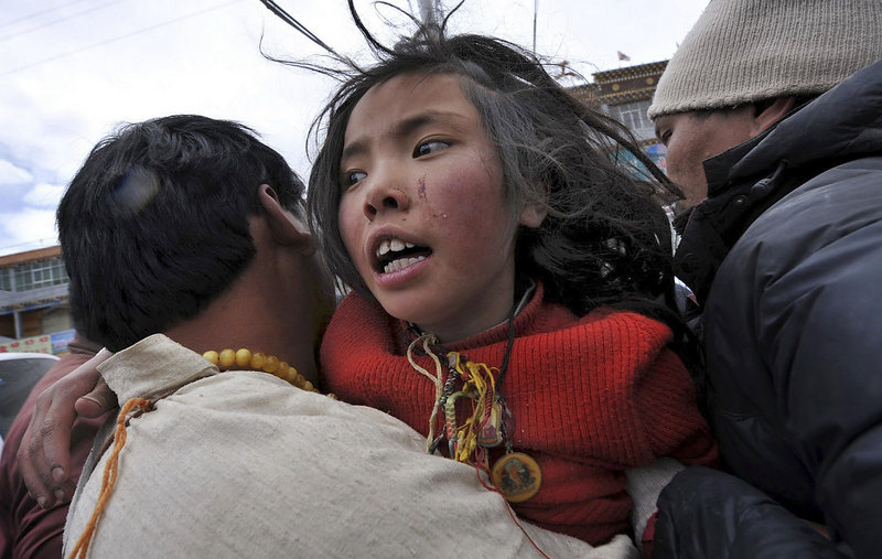A man carries an earthquake survivor who was rescued Friday after being buried in rubble for more than two days in Yushu county, Qinghai province, western China.