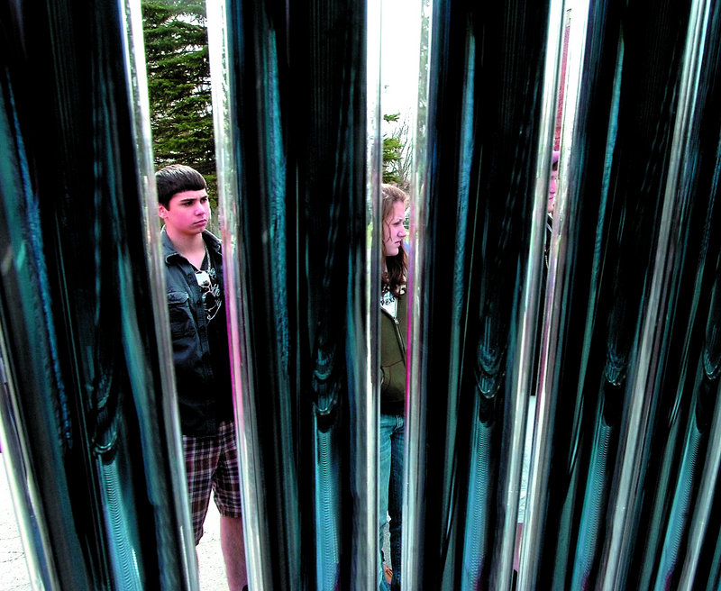 Maine Central Institute students are seen through the pipes of a solar hot water heater during a sustainability workshop Friday in Pittsfield.