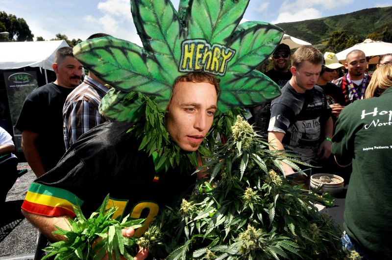 """Magic Ellingson, known as """"Henry Hemp,"""" smells a pot plant at the International Cannabis & Hemp Expo Saturday in Daly City, Calif. A proposal to legalize pot will be on this fall's state ballot."""