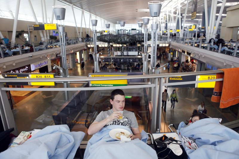 Huw Thomas, of England, eats breakfast in his cot at John F. Kennedy International Airport in New York on Monday. Thomas and his family were originally supposed to fly back to England from a vacation in New York on Friday.