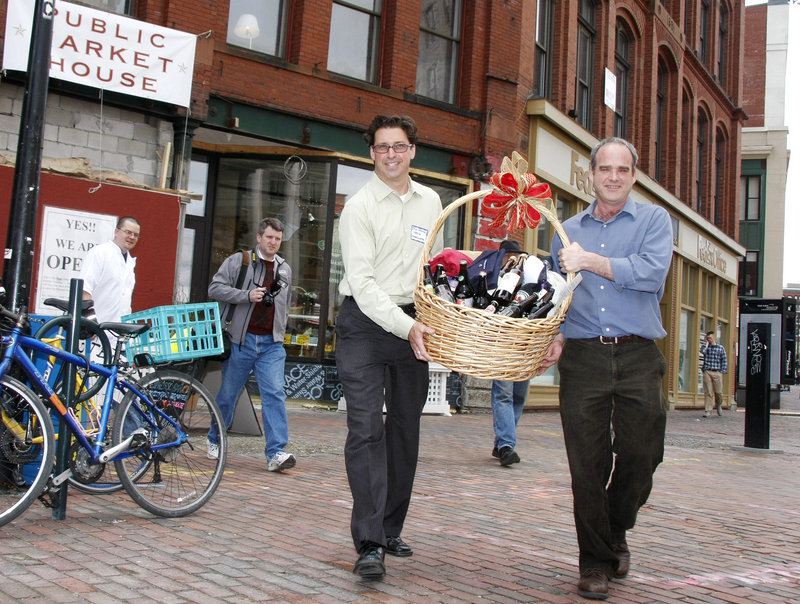 Paul Drinan, left, media coordinator, and Maine Beer and Beverage Corp. owner Bill Milliken carry a basket of assorted Maine brews from the Public Market House out to a car in Monument Square, to begin its journey to President Obama on Monday.