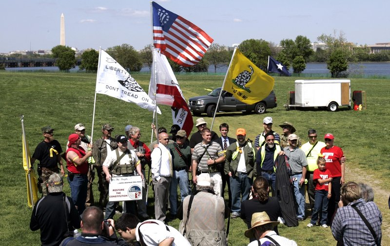 """Armed protesters gather for a group photo after holding a rally for First and Second Amendment rights at a """"Restore the Constitution"""" rally at Gravelly Point Park in Arlington, Va., on Monday. Like-minded but unarmed demonstrators also rallied in the nation's capital."""