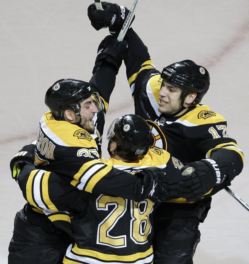Patrice Bergeron, left, is congratulated by teammates Mark Recchi, 28, and Milan Lucic after scoring what would be the winning goal against the Buffalo Sabres on Monday night at the TD Garden in Boston.