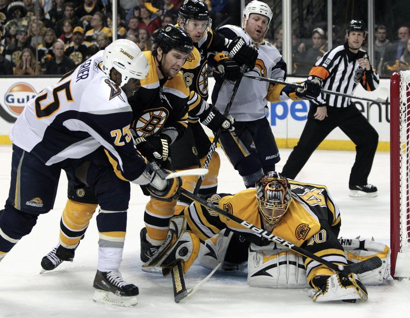 Bruins goalie Tuukka Rask covers the puck after an attempt by Buffalo Sabres right wing Mike Grier, left, as Bruins' Dennis Wideman, middle, holds him off Monday night.