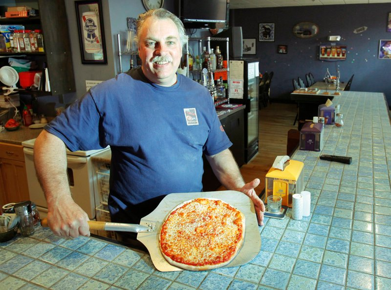 Jack Fowler prepares to serve a cheese pizza at Union House Pub and Pizza at the North Dam Mill in Biddeford.