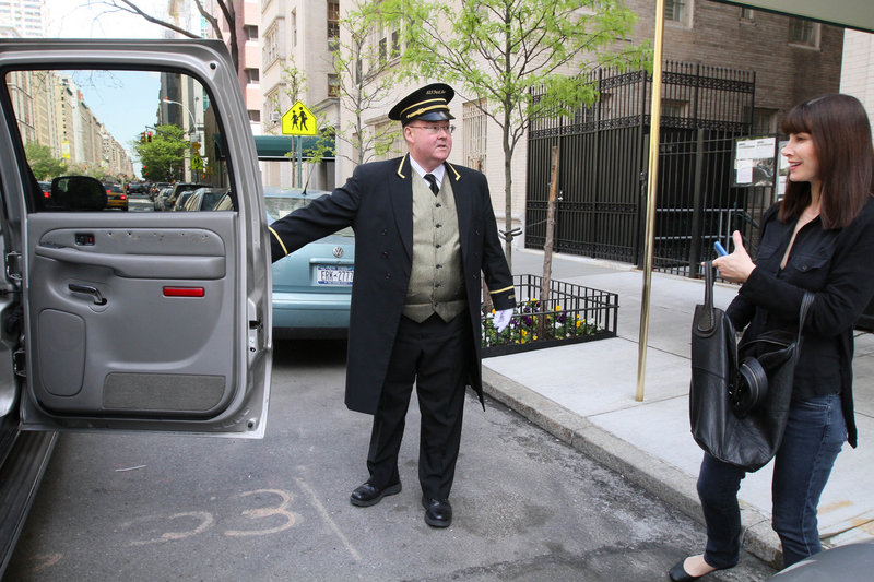 A concierge at a building on New York's Park Avenue holds the door for a woman as she gets into a car Tuesday. New Yorkers are bracing for a possible strike by 30,000 doormen, porters and other building workers who keep residential high-rises running smoothly.