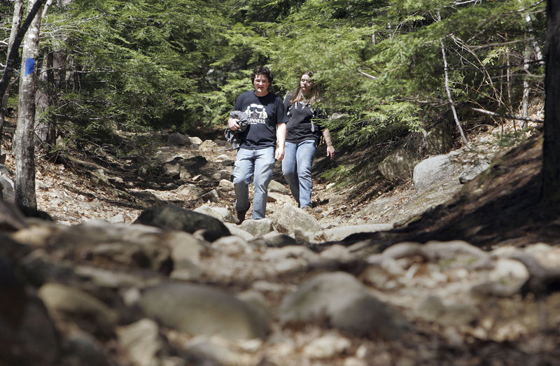 Charles Hughes and Amanda Dow hike down from Mount Major in Alton, N.H., last Wednesday. Researchers say transportation, income and accessibility can often be obstacles to participating in outdoor activity in rural New England.