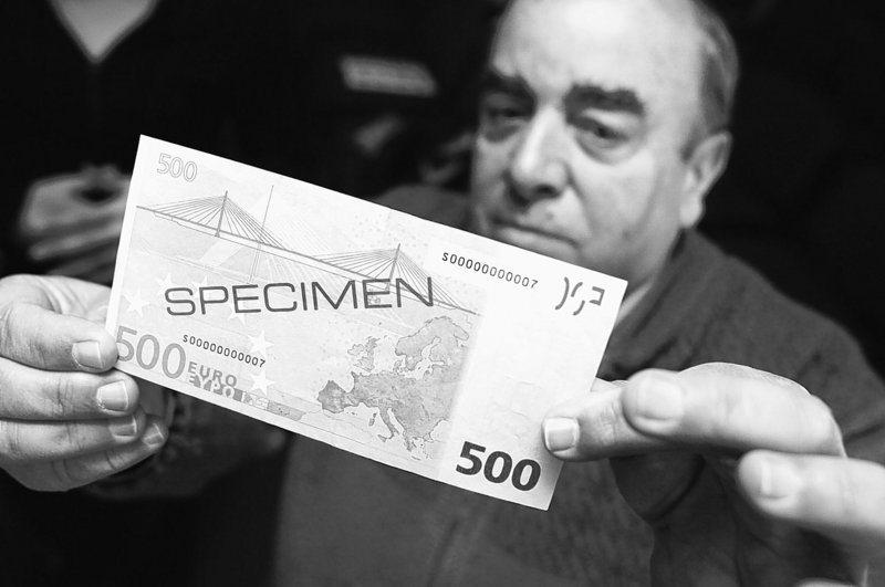 "Walter Muscat of Attard, Malta, inspects a specimen 500-euro note in 2007. A report by the Bank of Italy says the high-value bill ""simplifies the logistical management of large sums of money,"" making it a favorite of criminals."