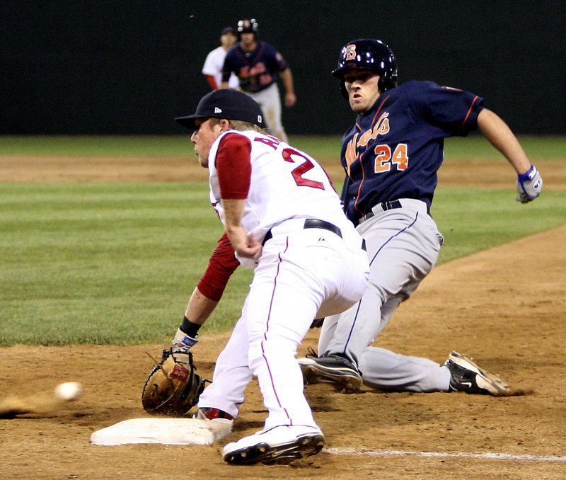 Portland pitcher Ryne Lawson tags out D.J. Wabick of the Binghamton Mets, who was attempting to score Tuesday night on a pitch that got away. Umpire Tom Honec prepares to make the call. Binghamton won, 15-3.