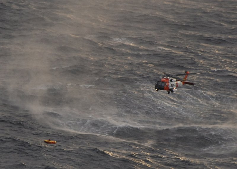 The crew of a Coast Guard helicopter prepares to rescue one of the four crew members from the Northern Belle in the Gulf of Alaska. The fishing vessel was hit by a swell and tipped on its side Tuesday night before sinking.