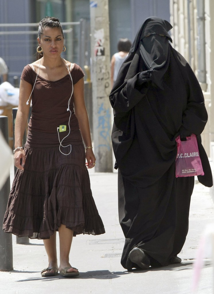 A conservative Muslim niqab, worn at right in Marseille, France, exposes only a woman's eyes. Muslim veils in public may be banned later this year.