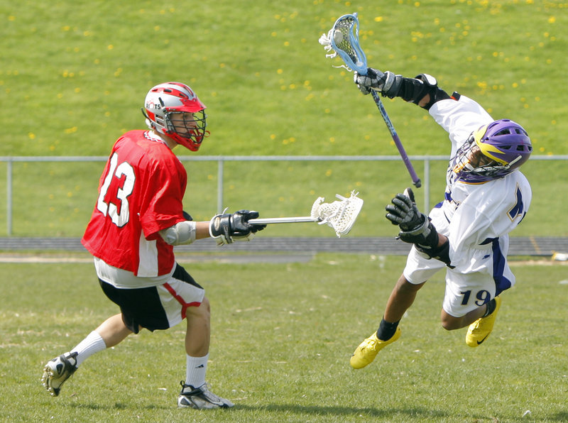 Garrett Naimie of Cheverus takes to the air Wednesday while advancing the ball against Chad Macleod of South Portland during South Portland's 8-3 victory in boys' lacrosse.