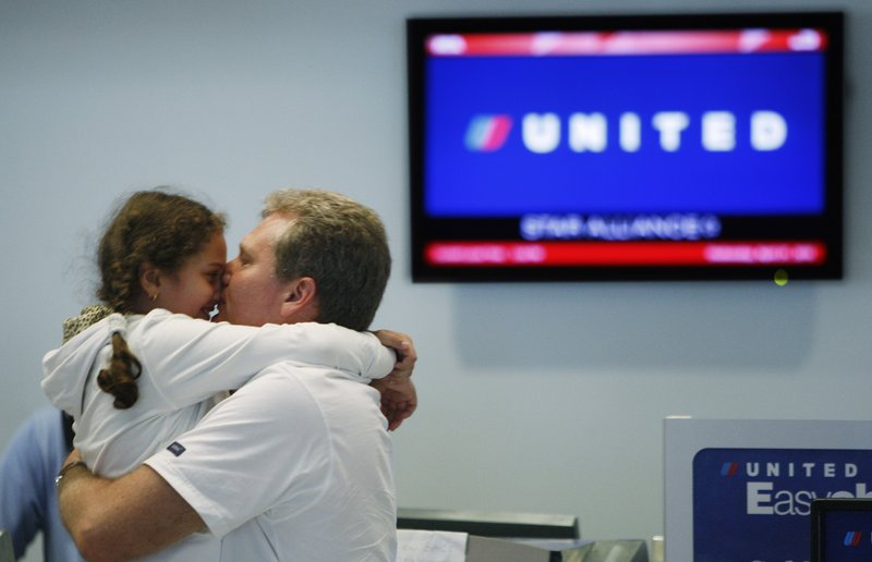 Andrey Zherikov kisses his daughter, Viktoria Zherikova, 7, as they wait at the United Airlines counter at Miami International Airport on Wednesday to find out if they can get a flight back home to Russia.