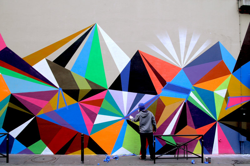 "Moore works on one of his ""vectorfunk"" designs in Paris. Recently he also painted a mural in New York City sponsored by Ray-Ban sunglasses. His work will be shown at Fore River Gallery in Portland beginning May 7."