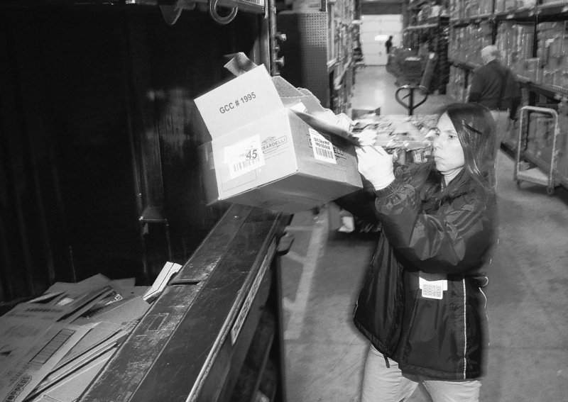 Julie Buczek throws used boxes into a compressor for recycling at a Cincinnati Walmart. The retailer is urging suppliers to reduce 20 million metric tons of greenhouse gas emissions by the end of 2015.