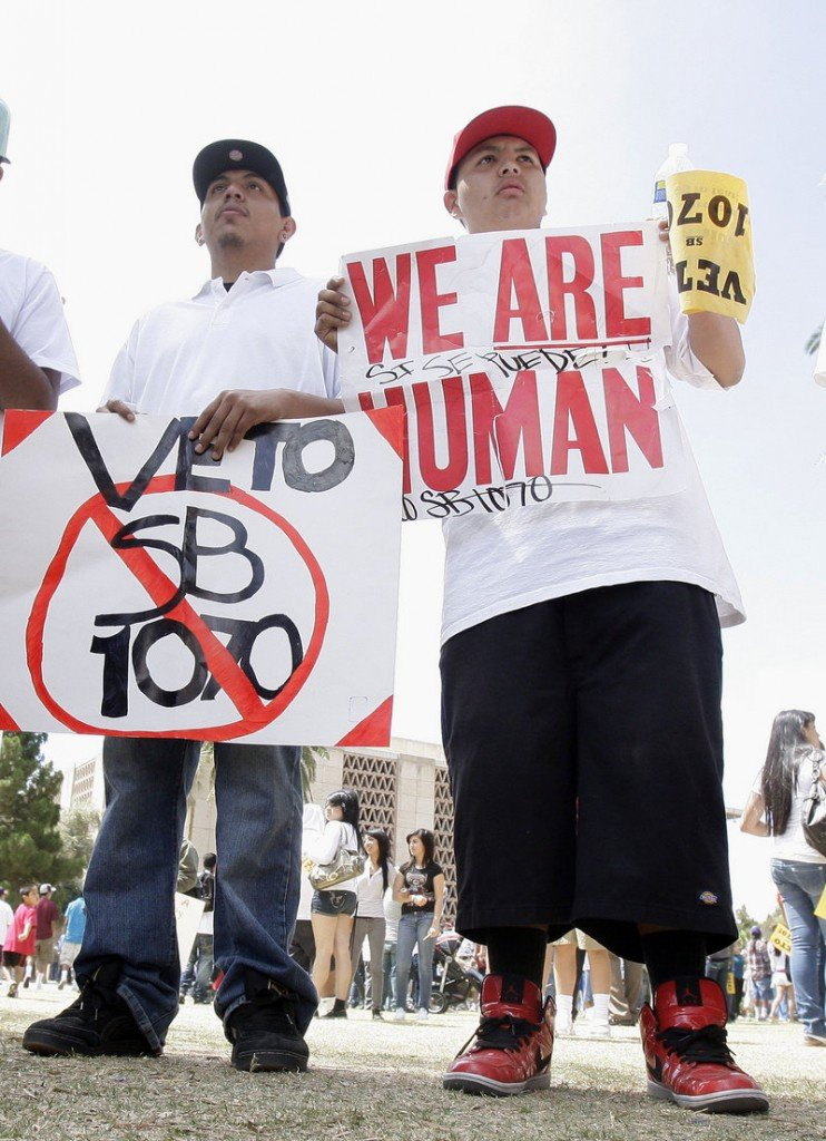 Edgar Rios, left, and Marcos Gonzalez rally against the Arizona immigration bill before it was signed into law Friday.