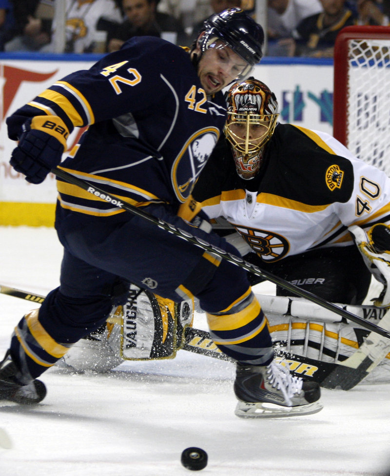 Nathan Gerbe of the Sabres tries to gain control of the puck in front of Bruins goalie Tuukka Rask during Buffalo's 4-1 victory Friday night.