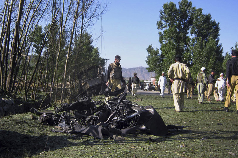 Pakistani policemen examine the site of a suicide attack on a prison van that wounded 10 officers Saturday in Timergarah.