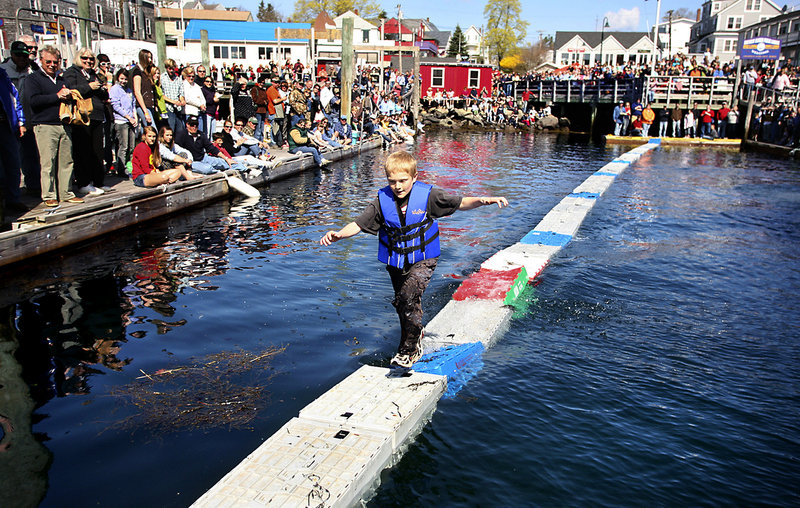 Nolin Conlin runs across crates filled with seaweed during the lobster crate-running competition. The competitors ran back and forth across the crates as fast as they could for three minutes without falling. Conlin finished second in the competition by running across 240 crates.