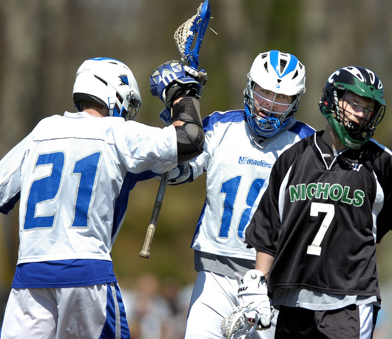 Eric Santos, left, congratulates Steven Beem after Beem's third-quarter goal. Santos opened the scoring for UNE just 13 seconds into the game and also scored in the final quarter.