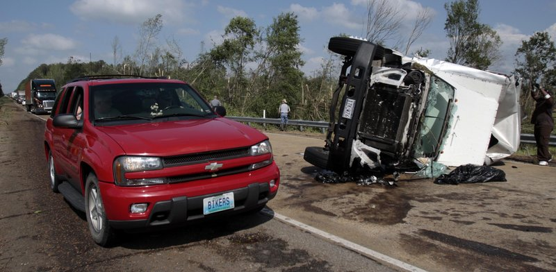 The Associated Press A motorist drives past an overturned truck which was among several vehicles damaged when a tornado crossed Interstate Highway 55 south of Durant, Miss., on Saturday.