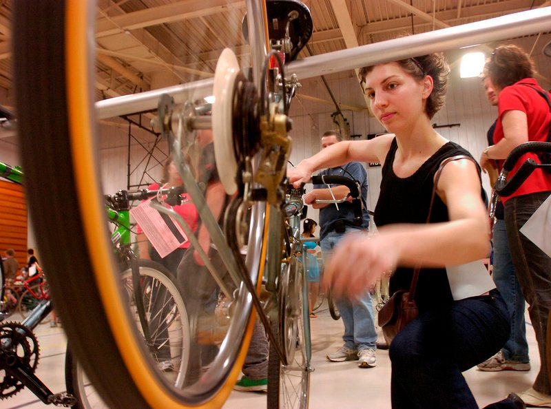 Rafaela Huonder of Portland checks out a road bike selling for $20 as the Greater Portland Bicycle Coalition held its annual bike swap Sunday in Sullivan Gymnasium at the University of Southern Maine in Portland.
