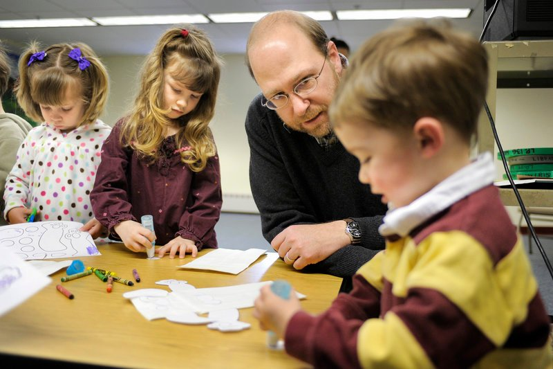 Reporter Ray Routhier helps Patrick Downey, 2, work on a craft project at Baxter Memorial Library in Gorham. At left are Michelle Meecham and Patrick's sister, Madeline, both 4.