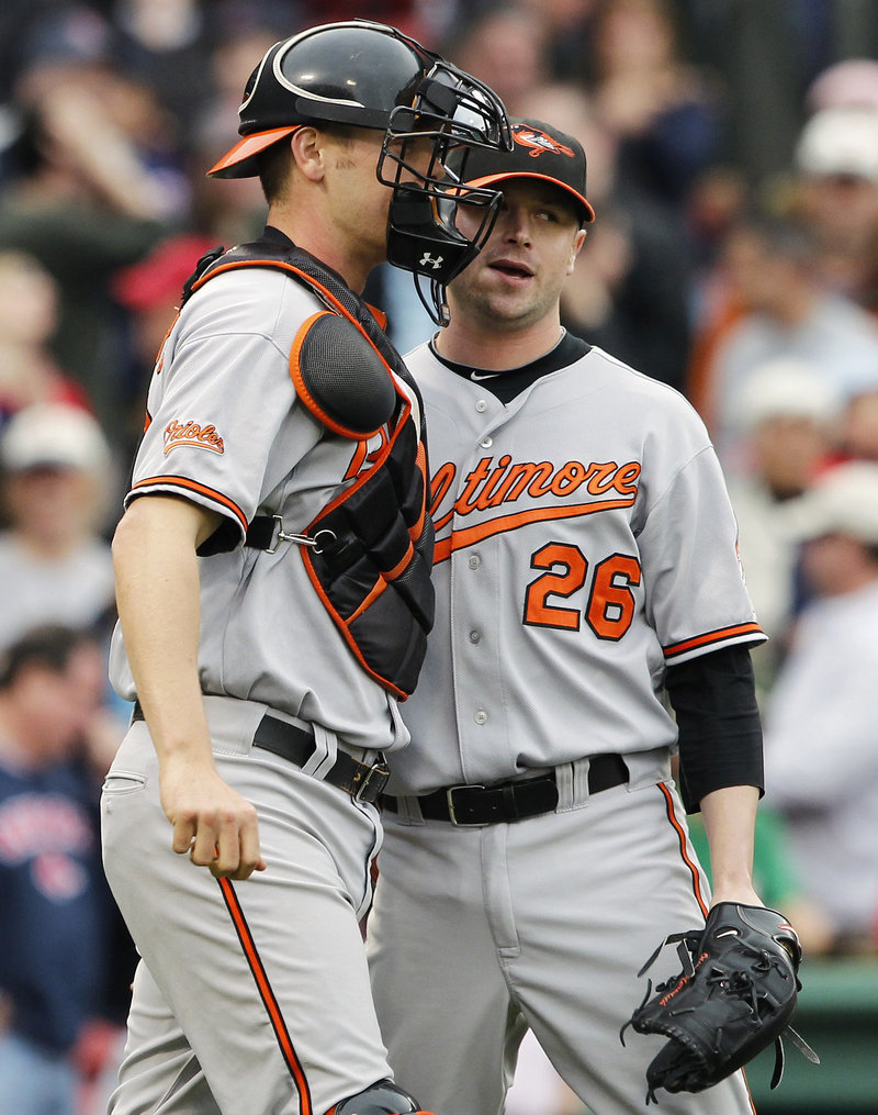 Orioles reliever Cla Meredith celebrates with catcher Craig Tatum after earning his first major league save Sunday in Baltimore's 7-6 win over the Red Sox.