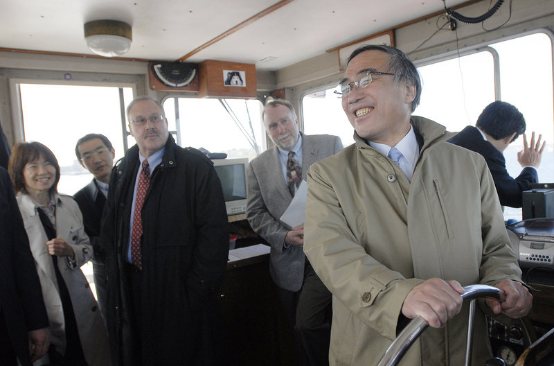 Takeshi Hamano, mayor of Shinagawa, Japan, steers the ferry Monday during a trip to Peaks Island. With him are dignitaries from Portland's sister city along with former Mayor David Brenerman, in dark coat, and Tom Morse, right, a relative of Edward Sylvester Morse, who is honored in Japan.
