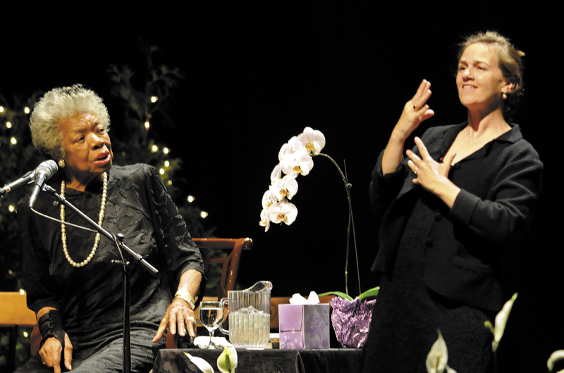 Maya Angelou, left, greets the crowd at the Augusta Civic Center with a song Monday. At right is sign language translator Margaret Haberman. The University of Maine at Augusta sponsored the poet's visit.