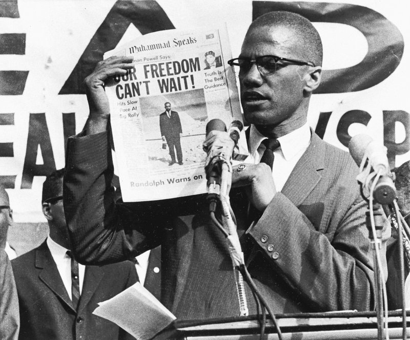 Black Muslim leader Malcolm X holds up a paper for the crowd to see during a Black Muslim rally in New York City on Aug. 6, 1963. One of his killers says Malcolm X was killed in 1965 out of anger at his split with the leadership of the Nation of Islam, the black Muslim movement for which he had once served as a prominent spokesman. Thomas Hagan says he has come to regret his role in the killing.
