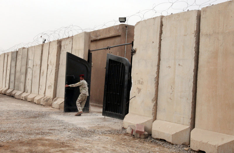 An Iraqi soldier closes the front gate to an Iraqi-run prison last week in Baghdad. New York-based Human Rights Watch says Iraqi men arrested last fall and accused of aiding and abetting terrorism were tortured at a secret prison.