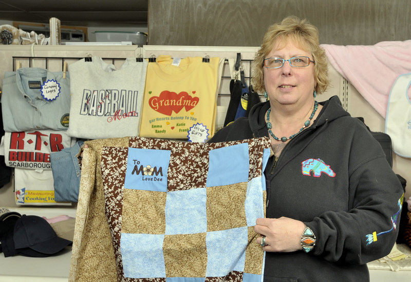 Candy Macomber, owner and operator of Passionate Stitches in Scarborough, shows embroidery she created on a customer's quilt – a feature she says a larger business does not offer. Her business niche is in making small orders for customers, but she can also do large orders on her $16,000 Tajima sewing machine.