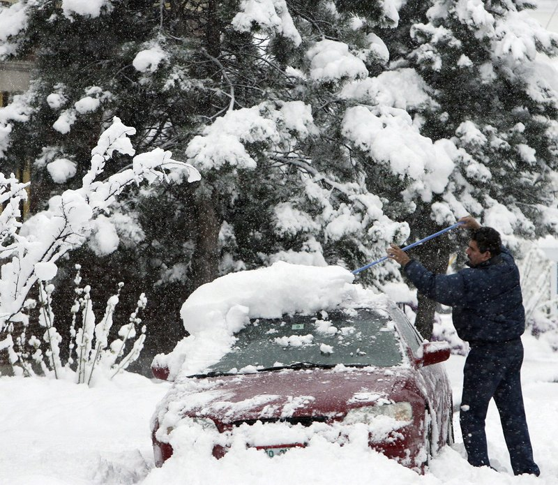 Perez Rios clears his car of snow Wednesday in Littleton, N.H. About 30,000 customers across northern New England and New York were without power at the peak of the storm