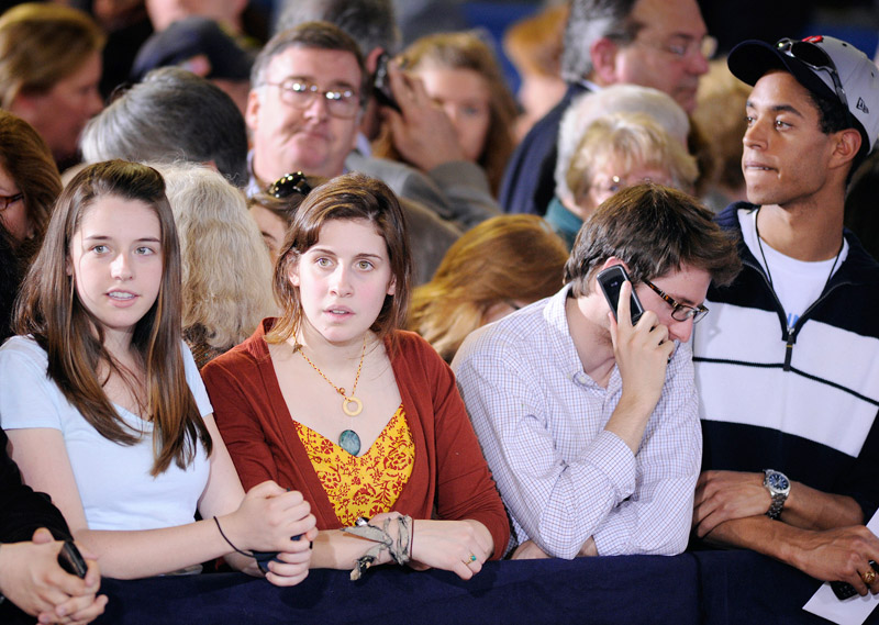 In the front row on the floor of the Portland Expo people await the arrival of President Barack Obama.