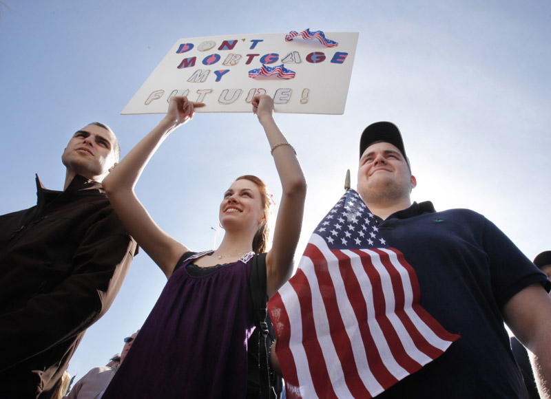 Corey Thompson of Spruce Head, Rebecca Harper of Cushing and Jacob Harper of Cushing listen to speakers at the Tea Party rally.