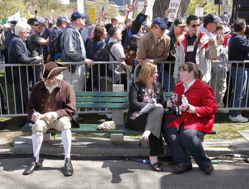 Jeff Cucci of Albion writes on cards on a bench at a Tea Party rally in Boston today. Cucci portrays Jacob Broom, a signer of the Constitution, at Tea Party rallies and events.