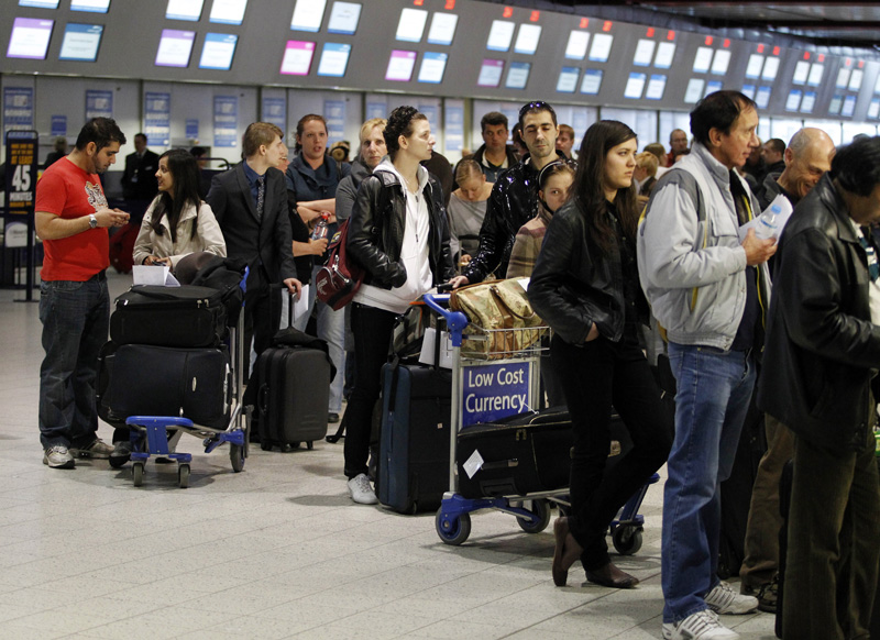 Passengers queue up in the departures area at Luton Airport in Luton, England, after Britain's Civil Aviation Authority said non-emergency flights would be banned in all airports until at least 1 a.m. Friday. Tens of thousands of passengers are stranded across Europe in one of most disruptive events to hit air travel in years.