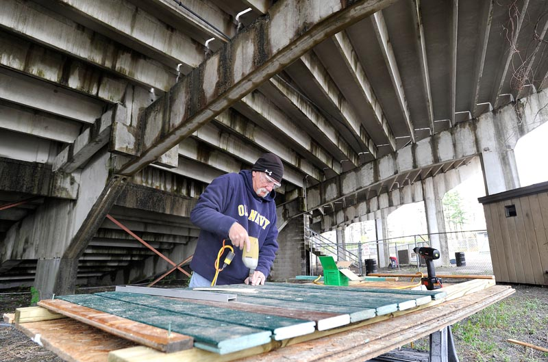Jack Sarnow repairs fencing as he and other volunteers clean up The Ballpark.