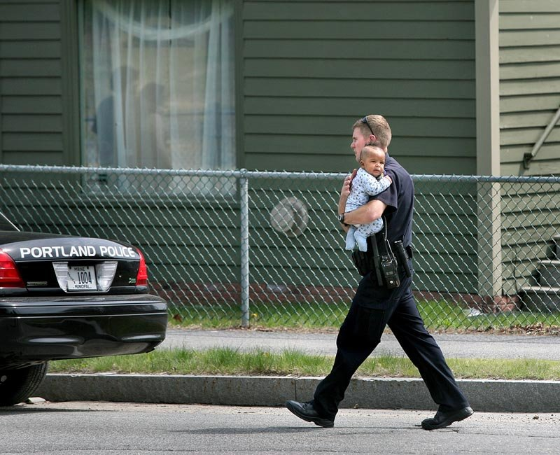 Portland Police Department negotiator Eric Nevins carries a 5-month-old baby to family members after the child was removed from an apartment during a police standoff on outer Forest Avenue on Sunday.