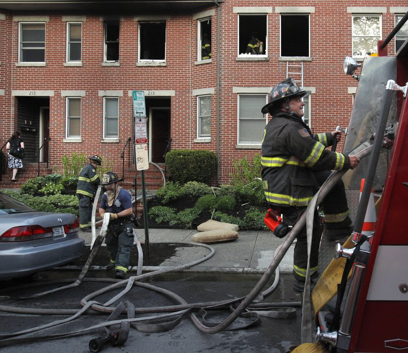Portland firefighters check their hoses Wednesday in front of 213 Vaughan St., where a fire damaged a second-floor apartment. No one was home at the time of the fire.